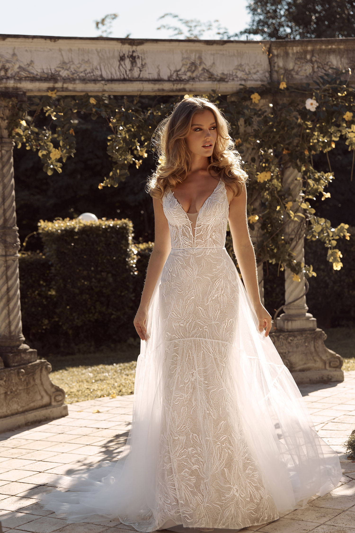 BAILEY ML19377 FULL LENGTH SLIM A-LINE SILHOUETTE FLORAL LACE WITH PLUNGING V NECKLINE AND FIT FLARE SKIRT WITH DETACHABLE OVERSKIRT INCLUDED WEDDING DRESS MADI LANE BRIDAL7